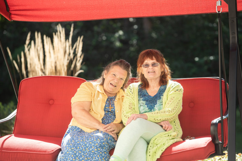 Two residents sitting on red swing