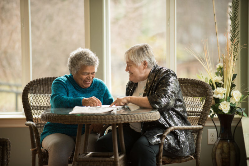Two female residents sitting at table and smiling together