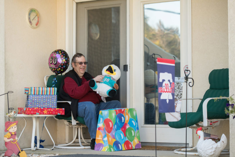 Male resident opening birthday gifts outside