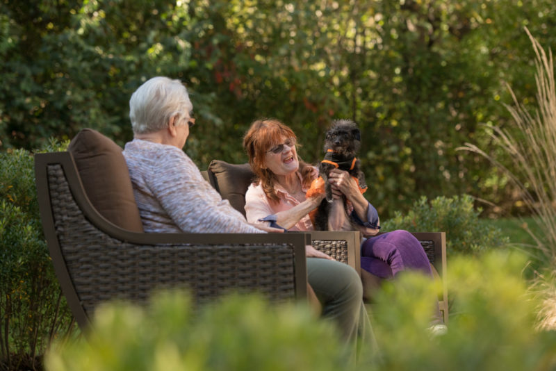 Two women sitting outdoors with a dog
