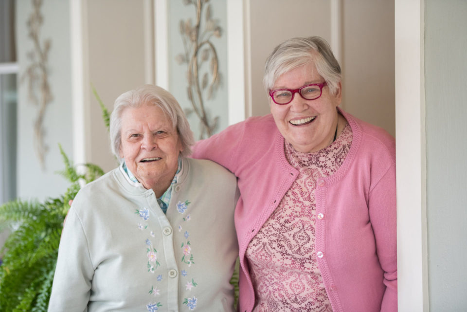 two residents smiling together